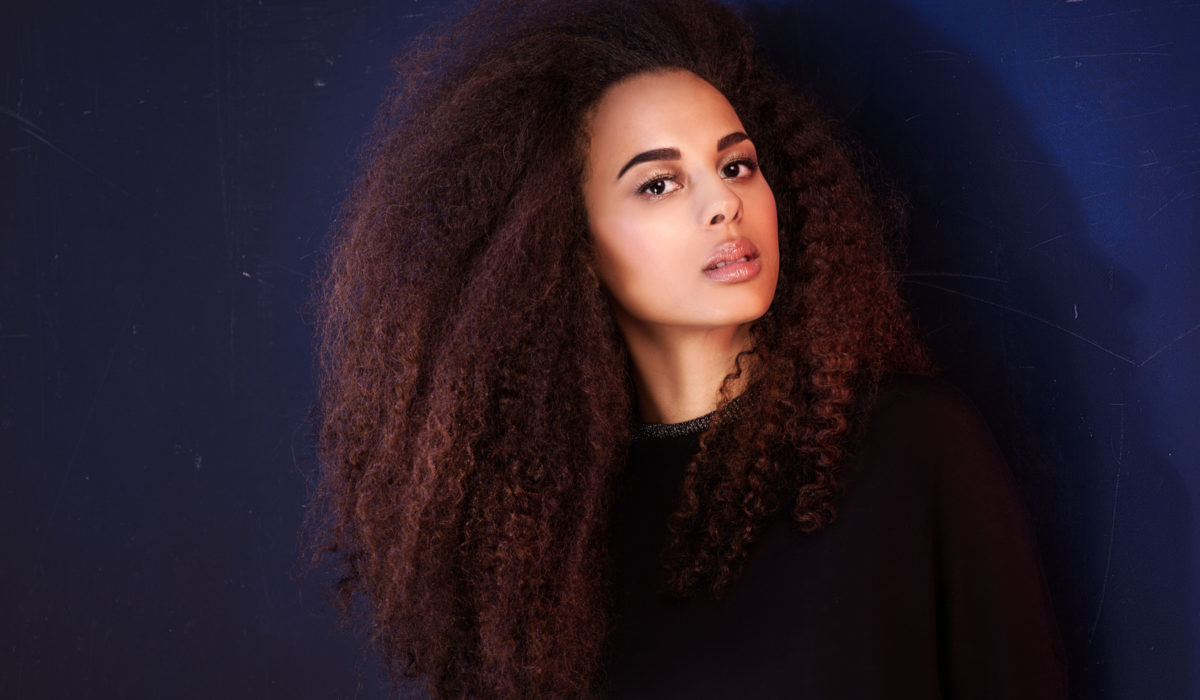 Beauty portrait of young attractive african american girl with brown eyes. Long curly hair. Girl looking at camera.